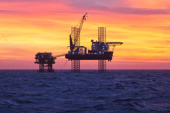 An offshore oil rig in open water at sunset.