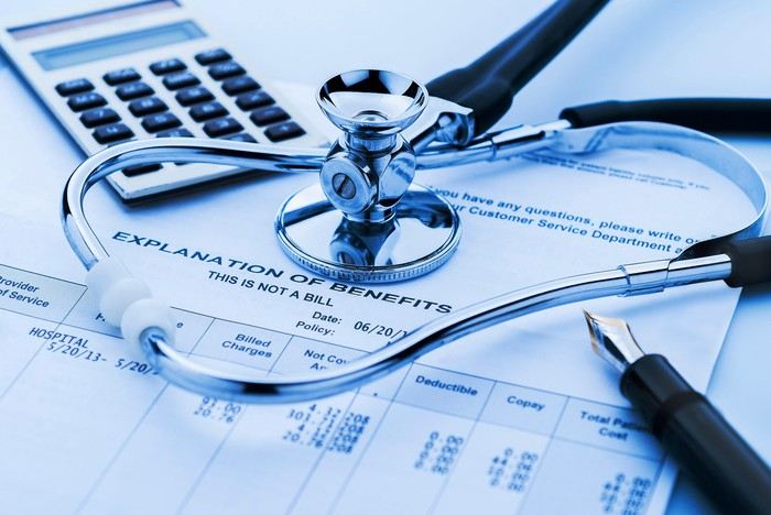 Explanation of health benefits with stethoscope and calculator.