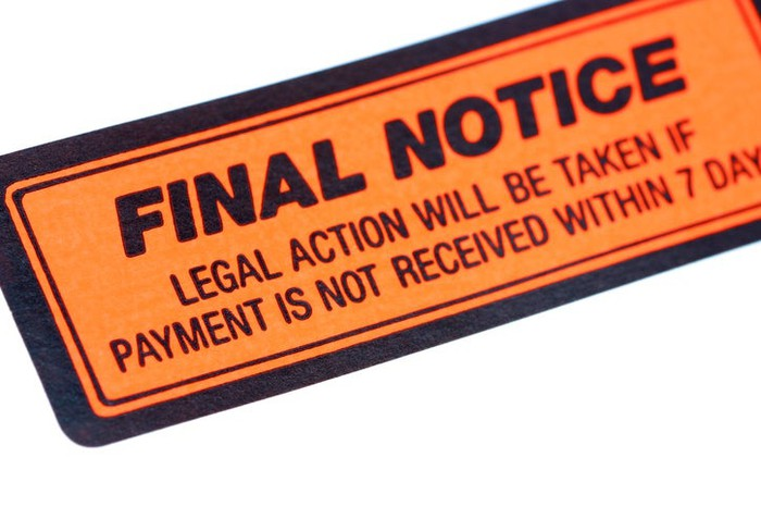 """An orange and black """"Final Notice"""" sticker, threatening legal action if payment is not received."""