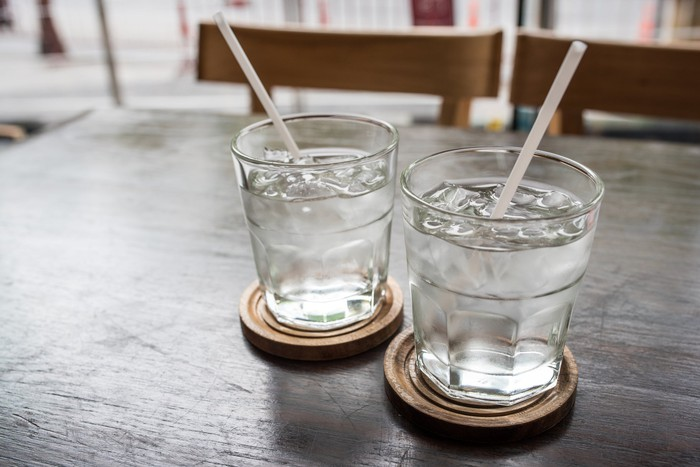 Two glasses of cold water with straws in them sitting on coasters on a wooden table.
