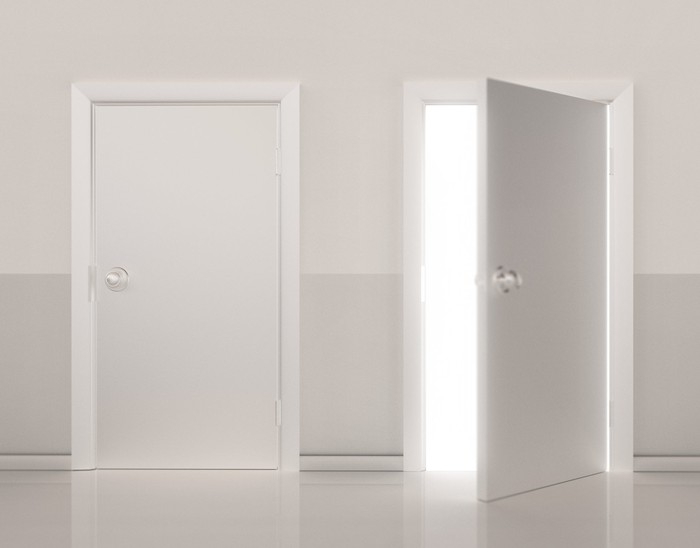 Two white doors with one closed and one partially open