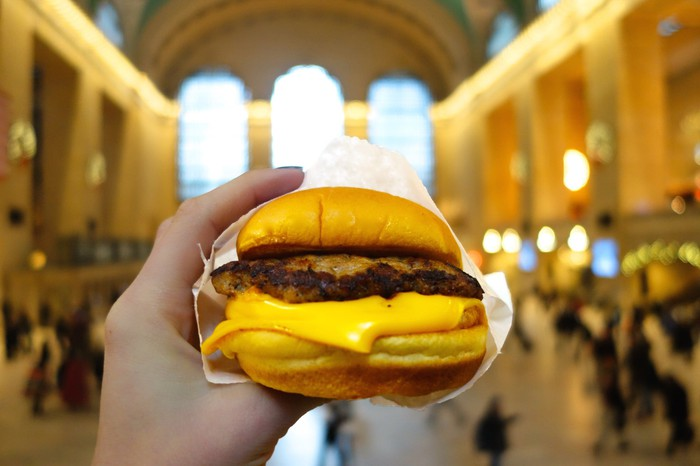 A hand holds up a Shake Shack cheeseburger, wrapped in paper.