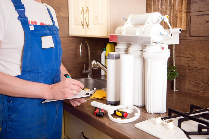 A plumber installing a water purification system in a kitchen