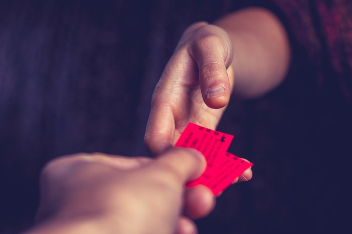 A hand giving two red tickets to another hand