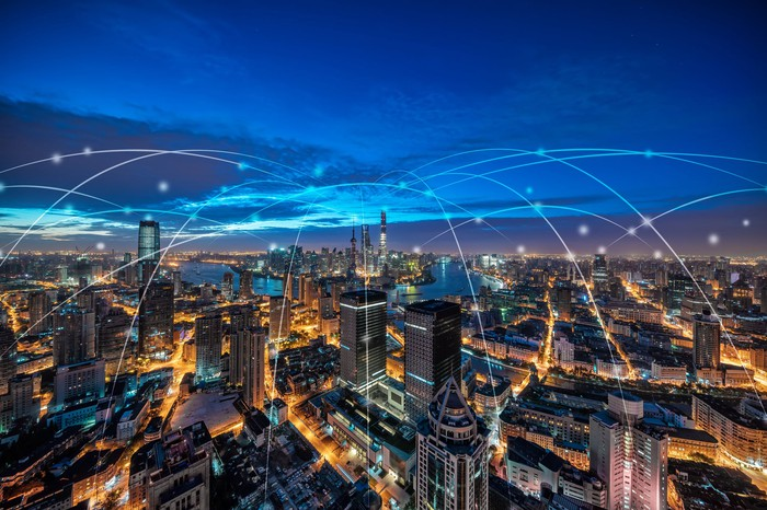 A city with white lines above it showing how everyone is digitally connected.