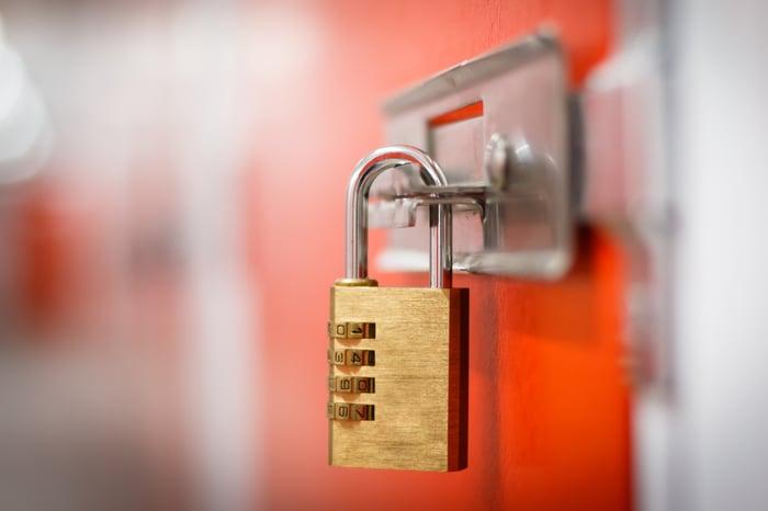 Padlock on an orange storage locker.