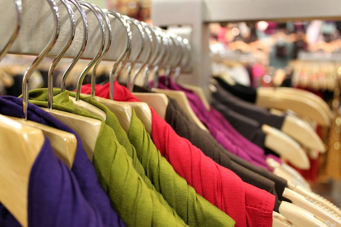 A rack of colorful dresses at a clothing store