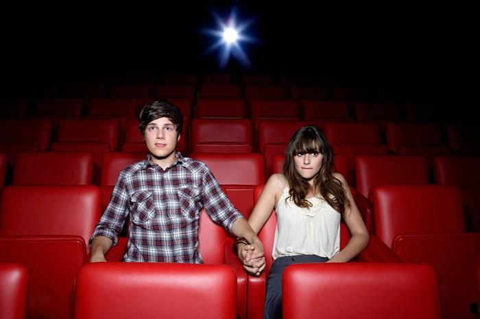 Young couple holding hands in a movie theater