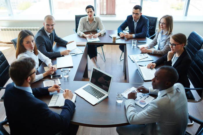 People in business attire sitting around a table in a meeting room.