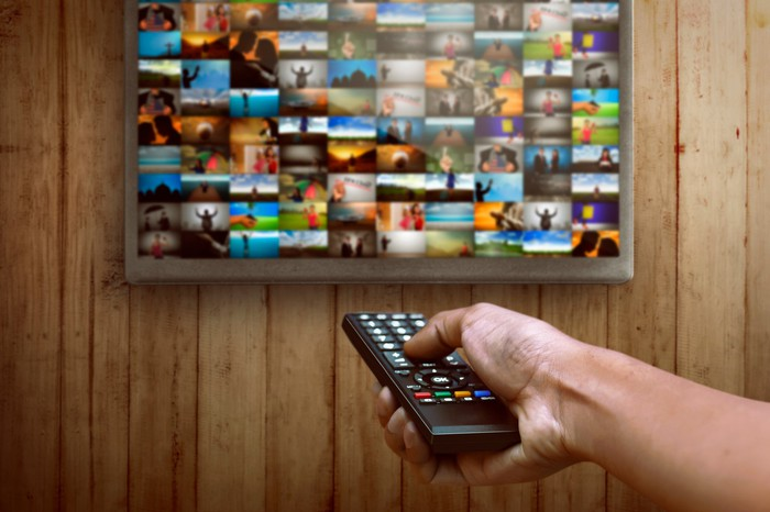 Person choosing channel on the television with remote.