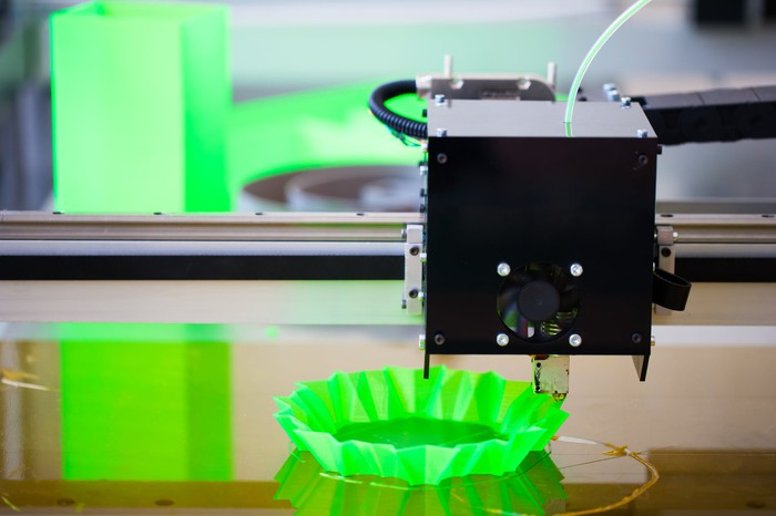 Close-up of a 3D printer printing an unidentifiable green plastic object.