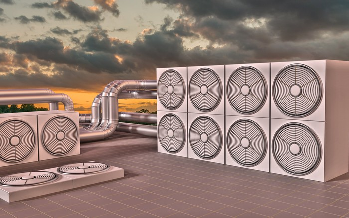 A cluster of industrial air conditioning units on the roof of a building, with a setting sun and cloudy sky in the background.