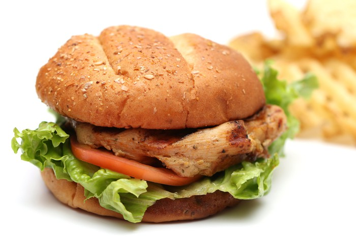 A chicken sandwich with waffle fries.