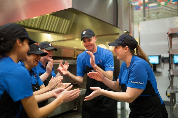 Domino's employees clapping during a meeting.