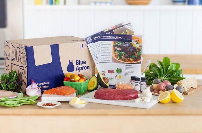 A Blue Apron box on a table, with ingredients and recipe cards displayed.