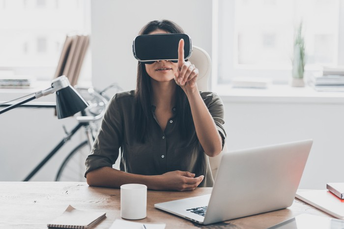 Woman sitting at desk wearing a virtual reality head and pointing her finger in the air.