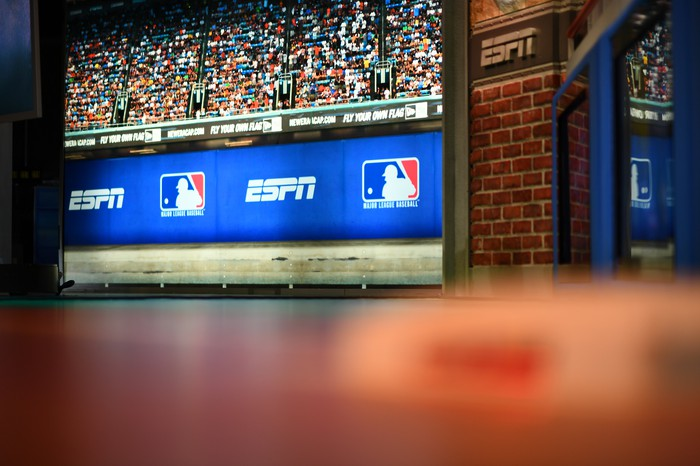 The set in an ESPN studio showing an image of an ESPN ad on a banner at a baseball game.