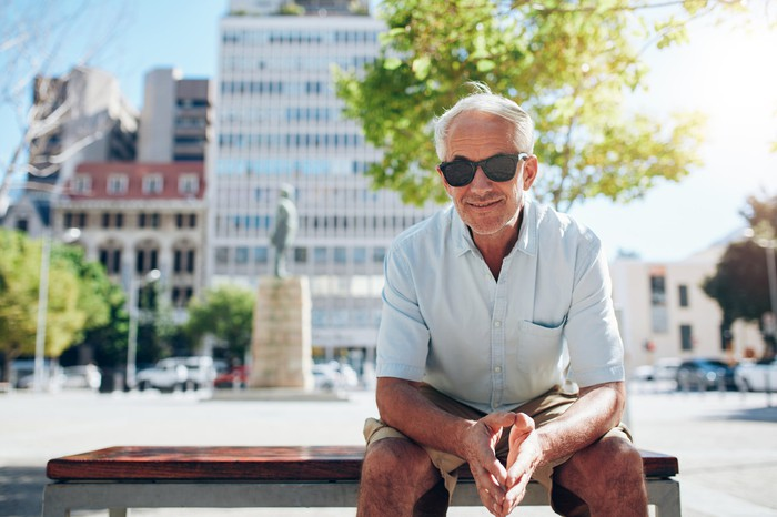 Senior male with sunglasses sitting on a bench