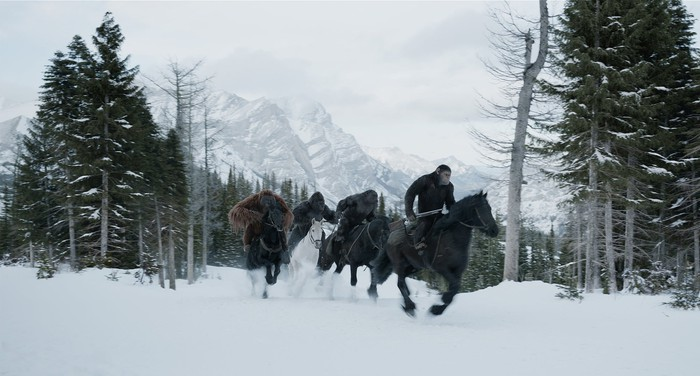 "Apes riding horses across a snowy landscape in Fox's ""War for the Planet of the Apes."""
