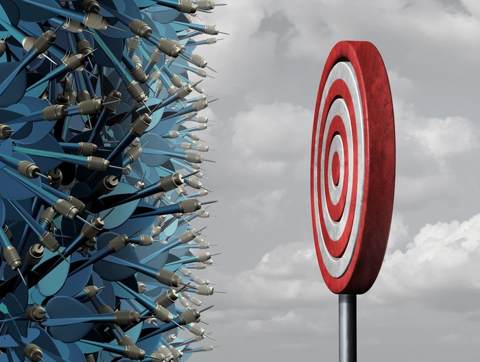 Dozens of blue darts crowded in front of a single, classic red-and-white dartboard target.