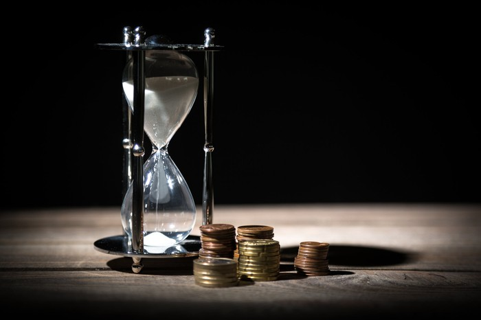 An hourglass and several stacks of coins on a table.