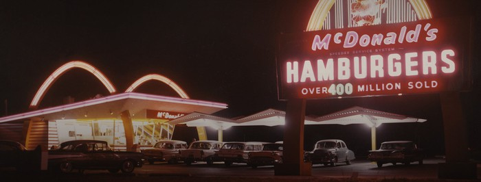 Old-school McDonald's restaurant at night, with a sign declaring more than 400 million burgers sold.