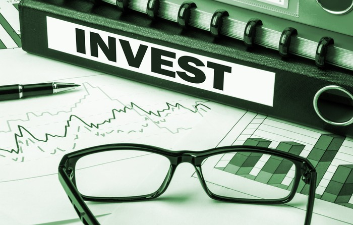 """A binder labeled """"invest"""" sits on top of a stock chart and next to a pen and pair of glasses."""