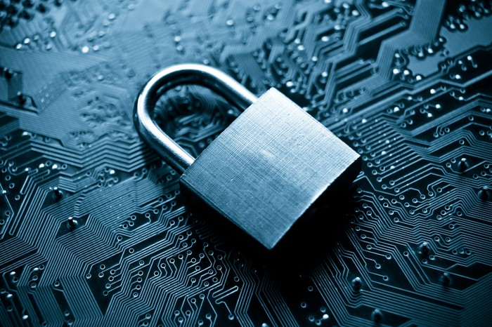Cybersecurity concept image, A steel padlock laying on a dark blue and black circuit board