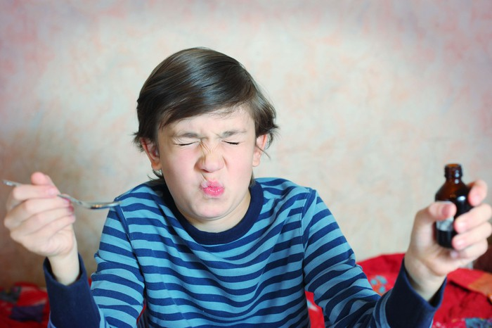 Boy grimacing after swallowing a spoonful of medicine.