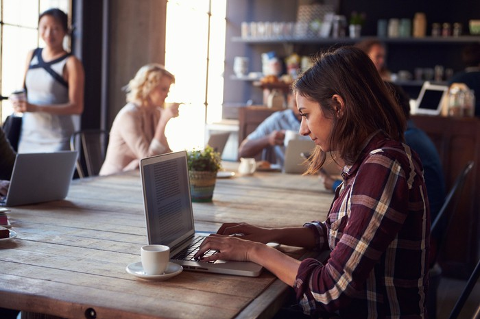girl working at laptop in coffeeshop, others there also on laptops