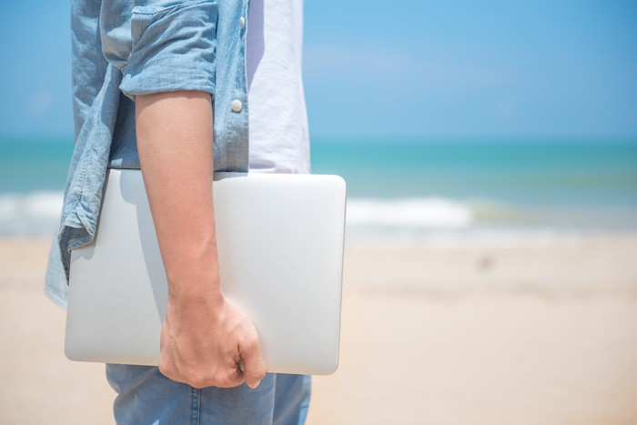 Man hand holding laptop at the beach
