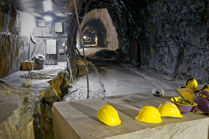 An underground mine, with yellow hard hats resting on a surface.