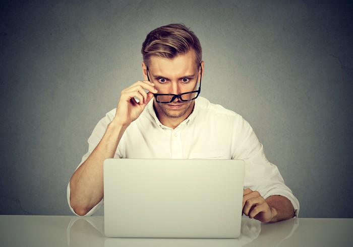 A man at a desk staring at his laptop, pulling his glasses down as he's surprised about what's on the screen.