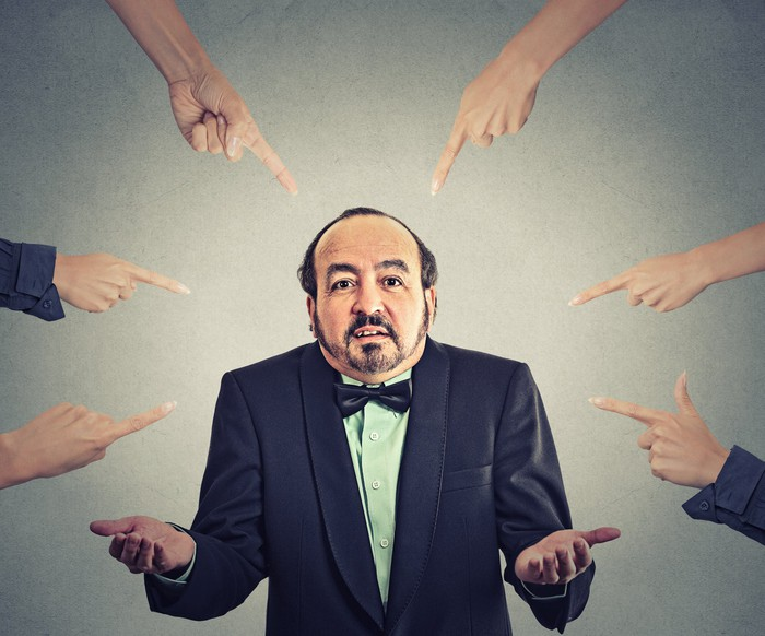 man in suit being pointed at by many fingers
