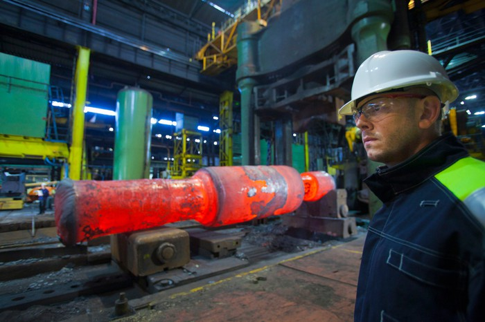 A worker standing in a steel forge