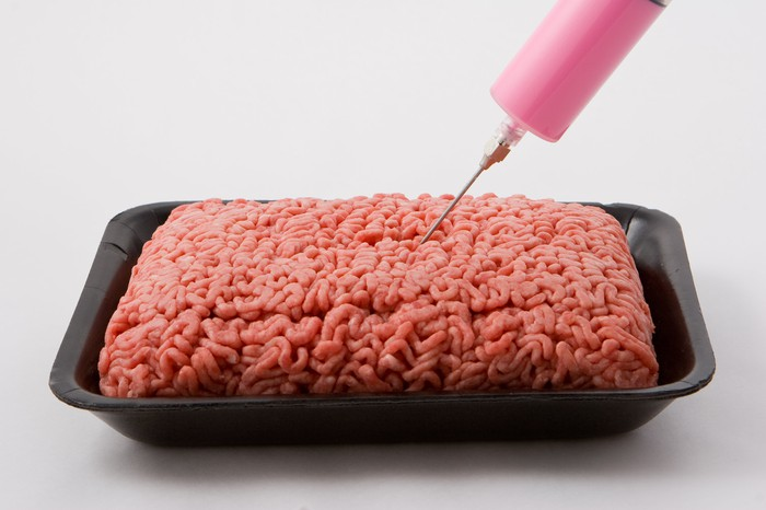 Pink liquid being injected into ground beef