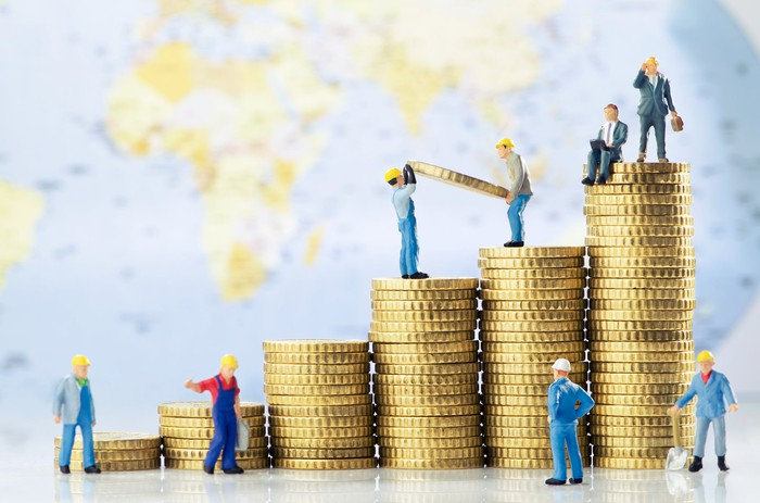 Toy construction workers and businessmen wearing hard hats and building successively higher columns of coins.