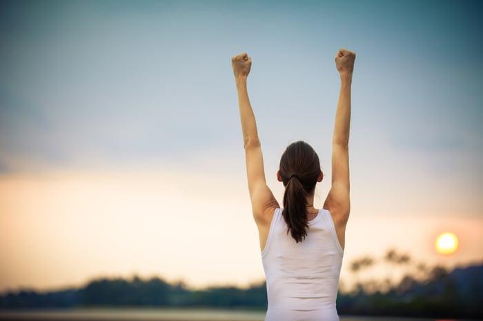 A woman raises her arms in triumph