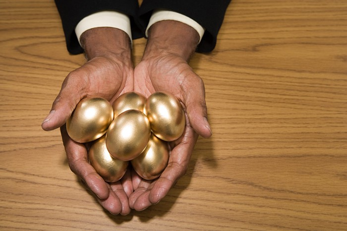 Man's hands resting on a wood table holding several golden eggs