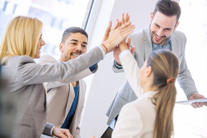 Four coworkers high-fiving one another