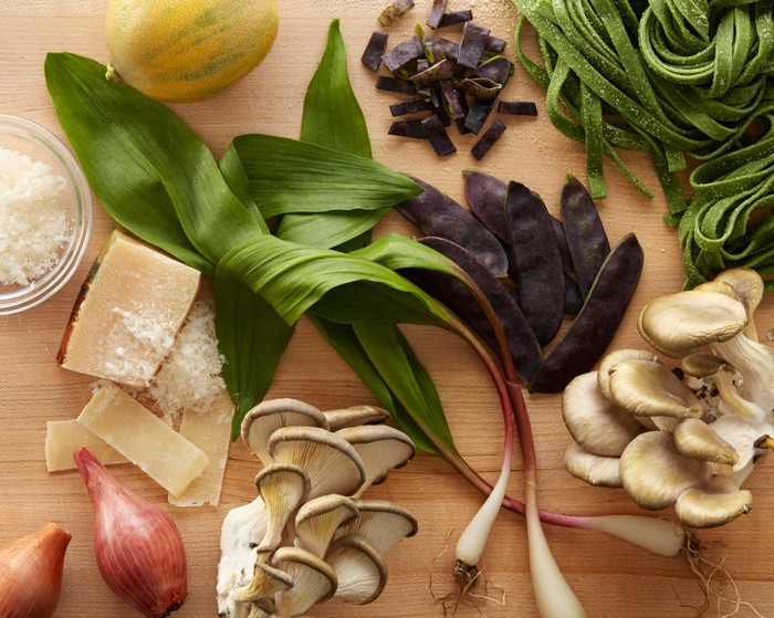 Pasta, cheese, mushrooms, and various vegetables laid out on a wooden surface.