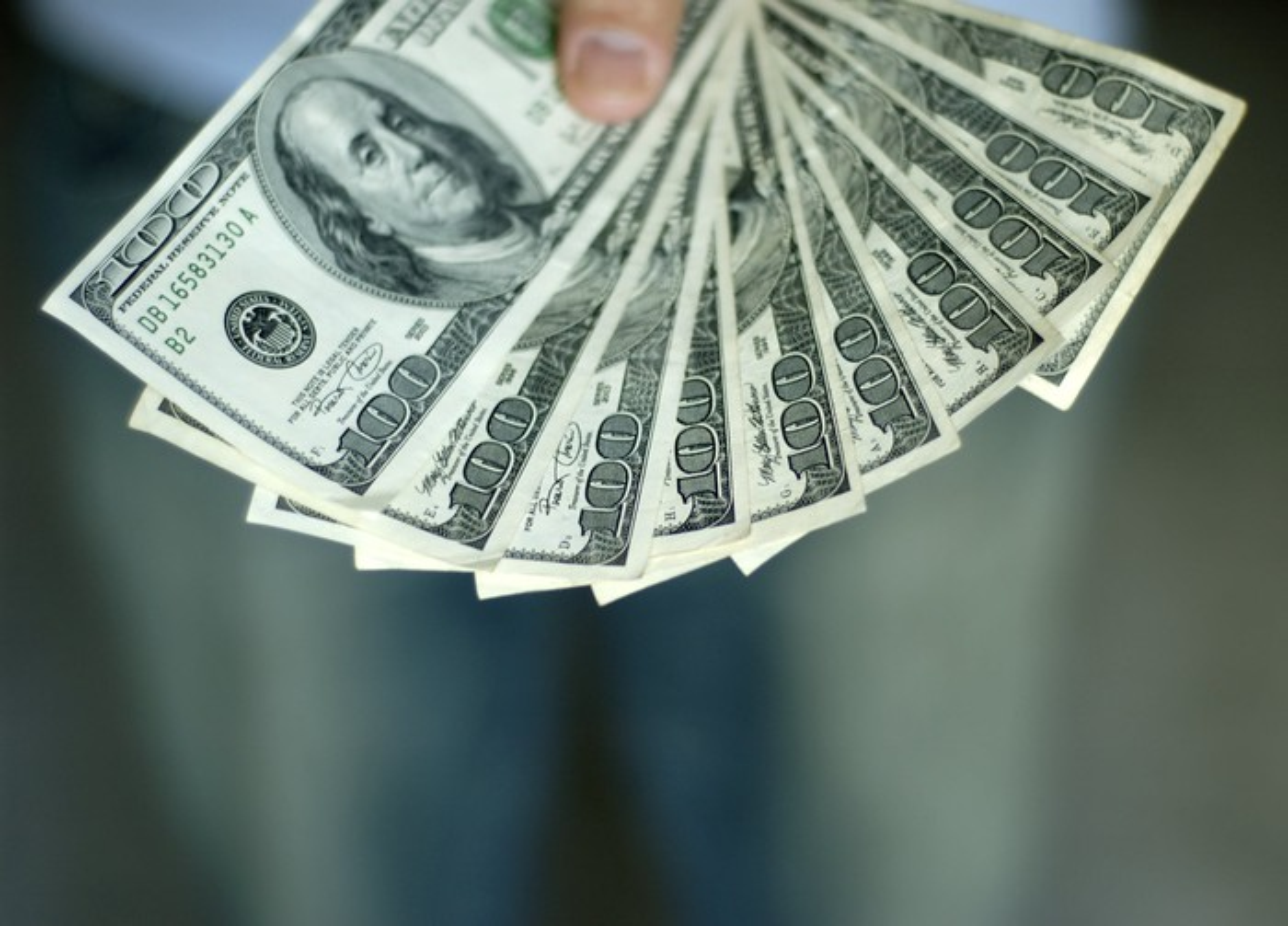 Hand holding 10 hundred-dollar bills.