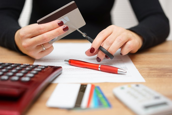Woman cutting up credit card with scissors.