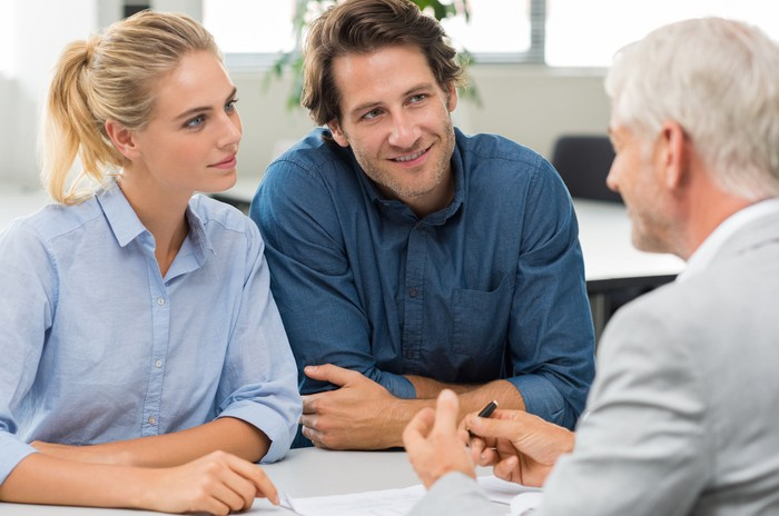 A financial advisor speaking with a younger couple.