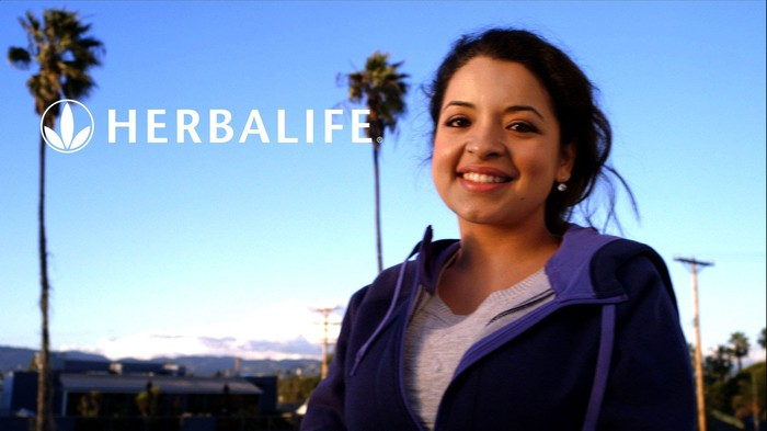 Woman in front of palm trees with Herbalife logo superimposed.