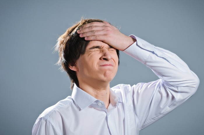 man in collared shirt slapping forehead and wincing