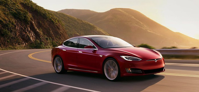 red Tesla car driving on curvy road