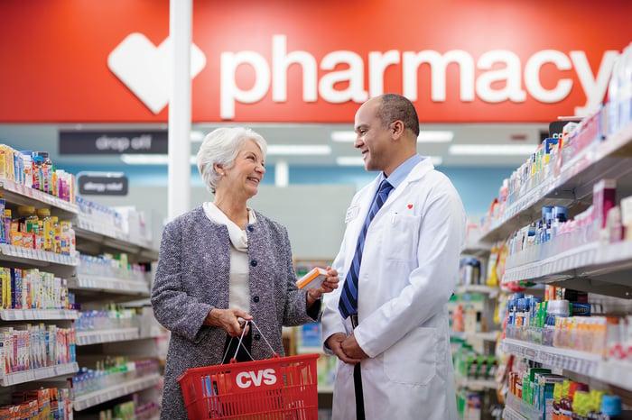 CVS pharmacist in white lab coat assists elderly female customer in store aisle.