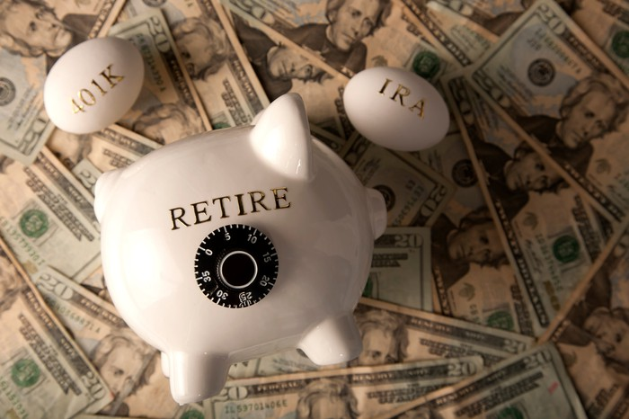 "Piggy bank with the word ""retire"" on it. Eggs with ""401k"" and ""IRA"" written on them. All on top of $20 bills"