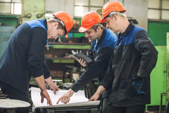 Three men looking over blueprints